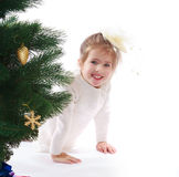 Pretty girl in a Christmas tree royalty free stock image