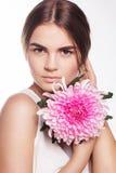 Pretty girl with chrysanthemum flower near face Stock Photo