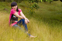 Pretty girl in citrus orchard. A graceful and pretty chinese girl was sitting in the citrus orchard which with full of yellow weeds stock photos