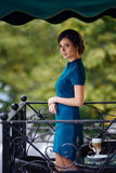 Pretty girl in classic elegant dress standing on the terrace of the summer cafe going to drink coffee. Stock Photography