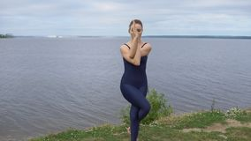 Pretty girl in classical yoga pose, energy concentration. Cloudy sky and lake on background. sport, yogi, meditation and healthy lifestyle concept stock video footage