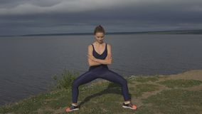 Pretty girl in classical yoga pose, energy concentration. Cloudy sky and lake on background. sport, yogi, meditation and healthy lifestyle concept stock video
