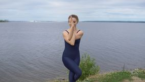 Pretty girl in classical yoga pose, energy concentration. Pretty young girl in classical yoga pose, energy concentration, cloudy sky and lake on background stock video