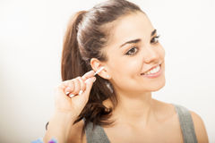 Pretty girl cleaning her ears in a bathroom Royalty Free Stock Photography