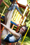 Pretty girl on climbing frame in park Stock Image