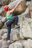 Pretty girl climbing rock face Royalty Free Stock Image