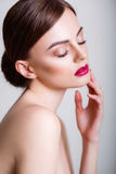 Pretty girl with closed eyes and dark hairs, with clean skin, with naked shoulders. A model with make-up and pink lips. Royalty Free Stock Photography
