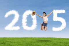 Pretty girl with cloud forming number 2015 Stock Photo