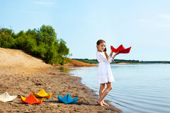 Pretty girl and colorful paper boats in park Royalty Free Stock Photo