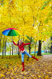 Pretty girl with colorful umbrella in autumn park Royalty Free Stock Images