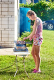 Pretty girl cooking barbecue outdoors Stock Image
