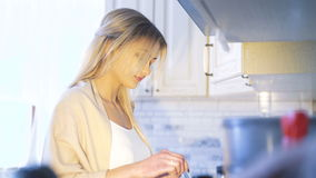 Pretty girl cooking at gas stove in 4K stock footage