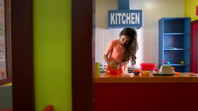 Pretty girl cooking hamburger in toy kitchen. stock video footage