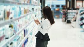 Pretty girl in cosmetics shop chooses face cream, reads ingredients, slow motion stock footage
