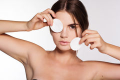 Pretty girl with cotton disc near her eyes. Beautiful woman with flawless skin is holding cotton pads near her eyes royalty free stock photo