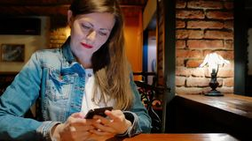 Pretty girl in a cotton jacket using smartphone in a cafe. Vintage interior. Brick wall. stock video footage