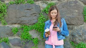 Pretty girl in a cotton jacket using smartphone and drinking coffee. Vintage wall of wild stone in the background. stock video footage