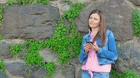 Pretty girl in a cotton jacket using smartphone with earphones. Vintage wall of wild stone in the background. stock video footage