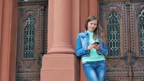 Pretty girl in a cotton jacket using smartphone. Vintage building in the background. stock footage