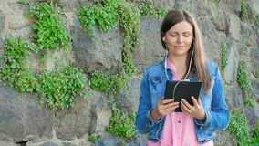 Pretty girl in a cotton jacket using tablet computer with earphones. Vintage wall of wild stone in the background. stock video footage