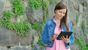Pretty girl in a cotton jacket using tablet computer. Vintage wall of wild stone in the background. stock video