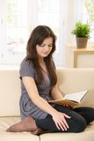 Pretty girl on couch with book Stock Images