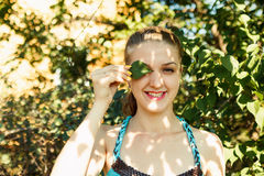 Pretty girl covering one eye by green leaf. Summer funny portrait Royalty Free Stock Photo