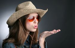 Pretty girl in cowboy hat. Blows on palm Royalty Free Stock Photos