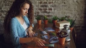 Pretty girl creative designer is putting photographs on wooden table then shooting flat lay pictures with smartphone. Modern technology, professional stock video