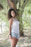 Pretty girl with curly hairs standing under the trees Royalty Free Stock Image