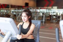 Pretty girl is cycling the bicycle machine at sport gym. Charmin royalty free stock image