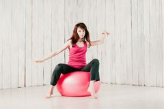Pretty girl dancing on a pink fitball, motion blur, high key stock photography