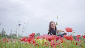Adorable young girl dancing in a poppy field holding flag of Germany in hands outdoors. Connection with nature. Pretty girl dancing in a poppy field holding the stock video