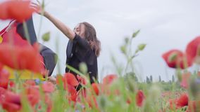 Cute adorable young girl dancing in a poppy field holding flag of Germany in hands outdoors. Connection with nature. Pretty girl dancing in a poppy field holding stock video