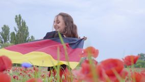 Cute adorable young woman dancing in a poppy field holding flag of Germany in hands outdoors. Connection with nature. Pretty girl dancing in a poppy field stock video footage