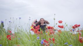 Pretty girl dancing in a poppy field holding flag of Germany in hands outdoors. Connection with nature, patriotism. Pretty girl dancing in a poppy field holding stock video footage