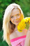 Pretty girl with dandelions in hands Stock Images