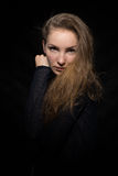 Pretty girl in a dark blue sweater. Over a black background Stock Photo