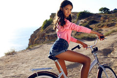 Pretty girl with dark hair in sport clothes sitting on bicycle Stock Photography