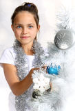 Pretty  girl decorates the Christmas tree Royalty Free Stock Photo