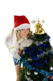 Pretty girl decorating christmas tree. Pretty girl wearing knitted mittens and santa hat decorating christmas tree Royalty Free Stock Image