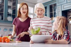 Pretty girl demonstrating salad recipe to mother and grandmother. Important help. Sweet little girl showing a recipe on the tablet to her mother and grandmother Stock Image