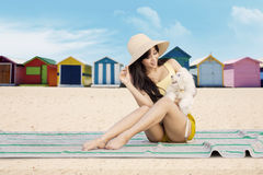 Pretty girl and dog sit on the beach Royalty Free Stock Image