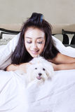 Pretty girl and dog under blanket. Mage of beautiful woman holding maltese dog while lying under a blanket in the bedroom Royalty Free Stock Photography