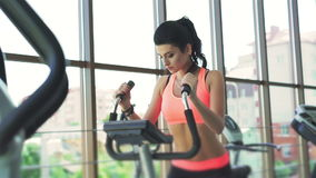 Pretty girl doing exercise with exercise bike in the gym stock video footage