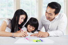 Pretty girl doing homework with parents Royalty Free Stock Photos