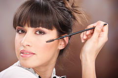 Pretty girl doing makeup. Pretty woman holding comb for eyelash stock images
