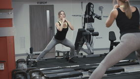 Pretty girl doing squats in the gym in 4K stock footage