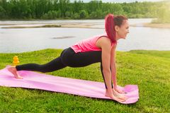 Pretty girl doing yoga exercises in the green park over lake. Concept of healthy lifestyle.  Stock Images