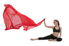Pretty girl doing yoga posing with red cloth Royalty Free Stock Images